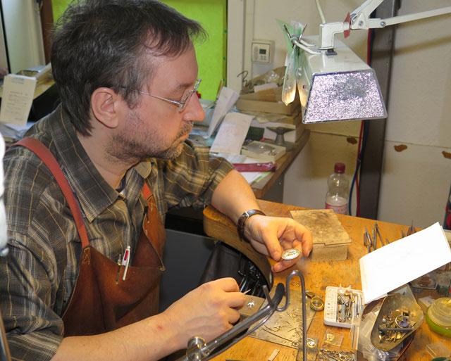 Goldschmiedemeister Jörg Iser arbeitet die Medaille in eine ovale silberne Fassung ein. Foto Scheffler