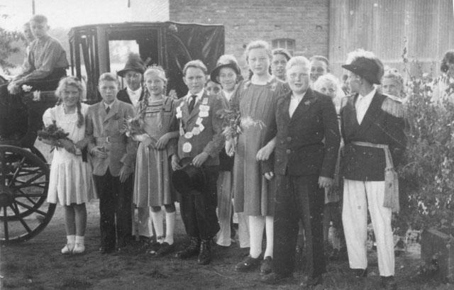 Vor 65 Jahren in Gahlen Auf dem Hof Neerfeld (v.l.): Ilse Ruloff, Egon Ufermann, Königin Gertrud Neerfeld, König Gustav Ruloff, Oberst Ernst Uhlenbruck, Kornelia Cappell, Manfred Höchst, Königsadjutant Walter Heidermann. Auf dem Kutschbock (v.l.): Ernst Eifert, Erich Janzen. RN-Repro Scheffler
