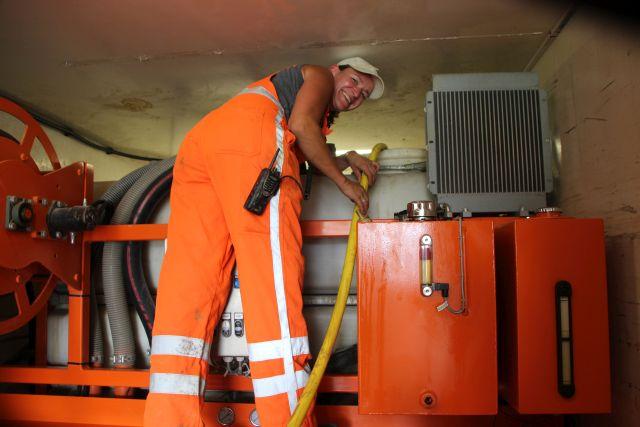 Chef in dem Hightec LKW ist eine Frau. Sie schiebt vom LKW die Rohre mit Druckluft durch die vorgebohrte Leitung.