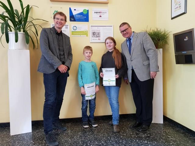 Schulleiter Norbert Hohmann (rechts) und der Fachkonferenz-Vorsitzende Mathematik Hendrik Meyer (links)  überreichen den erfolgreichen Teilnehmern Johanna Frauenholz (6b) und Julius Bergermann (5e) ihre Urkunden und gratulieren ihnen zum Weiterkommen.