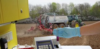 Nitratuntersuchung-vor-einem-Feld-mit-Traktor